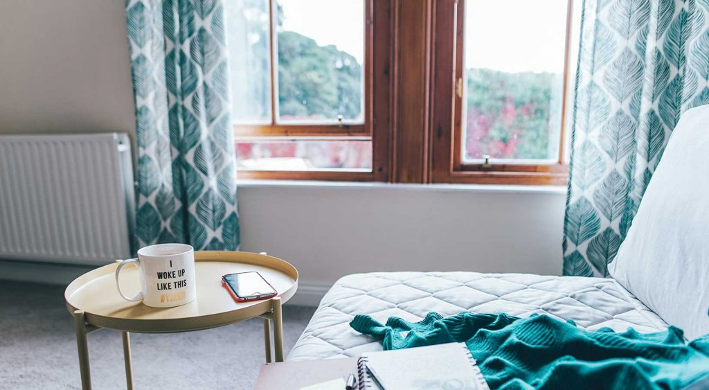 Daybed by a window and side table with coffee mug, iPhone, and journal