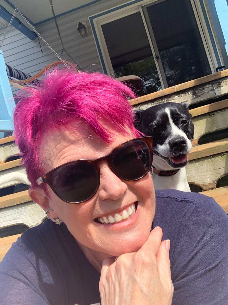 Robin Carberry, Business and Personal Development Coach, and her dog, Kelly sitting on the porch steps