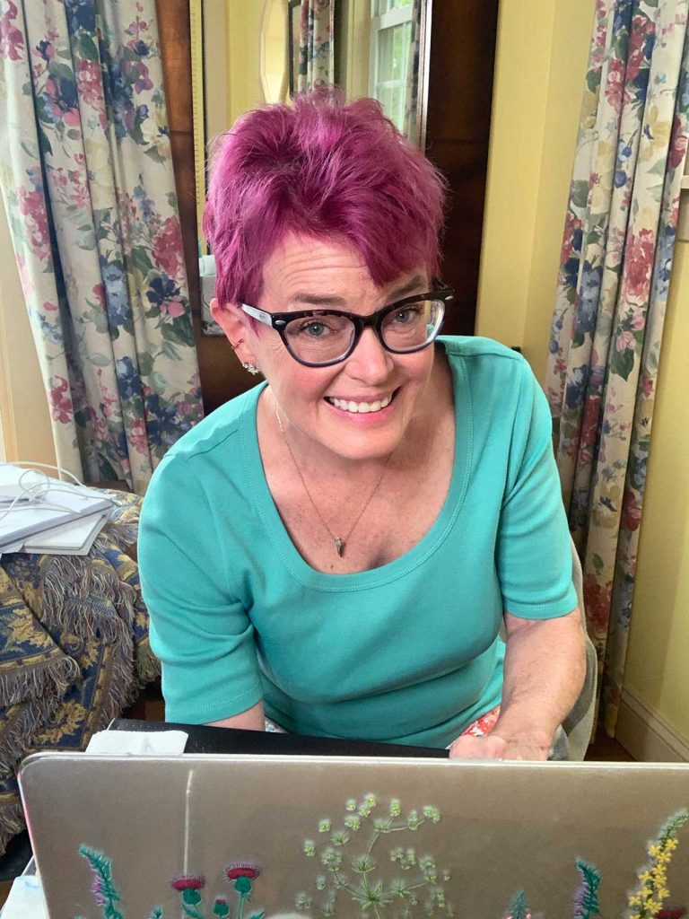 Robin Carberry working in her office at her laptop looking up and smiling
