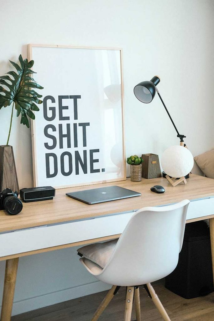 "desk and chair with closed laptop and poster that says ""get shit done"""