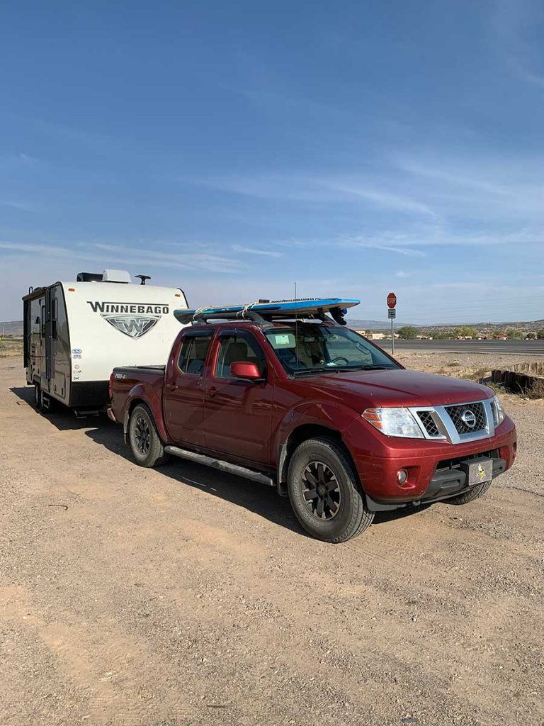 Red Nissan Frontier with a paddleboard on top pulling a Micro Minnie Winnebago