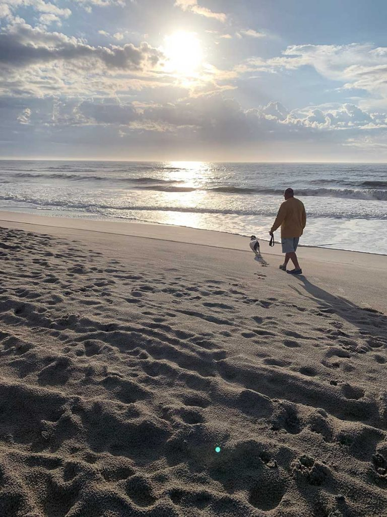 Ken Midyette and his dog, Kelly, on the walking by the ocean on a beach in Emerald Isle, North Carolina