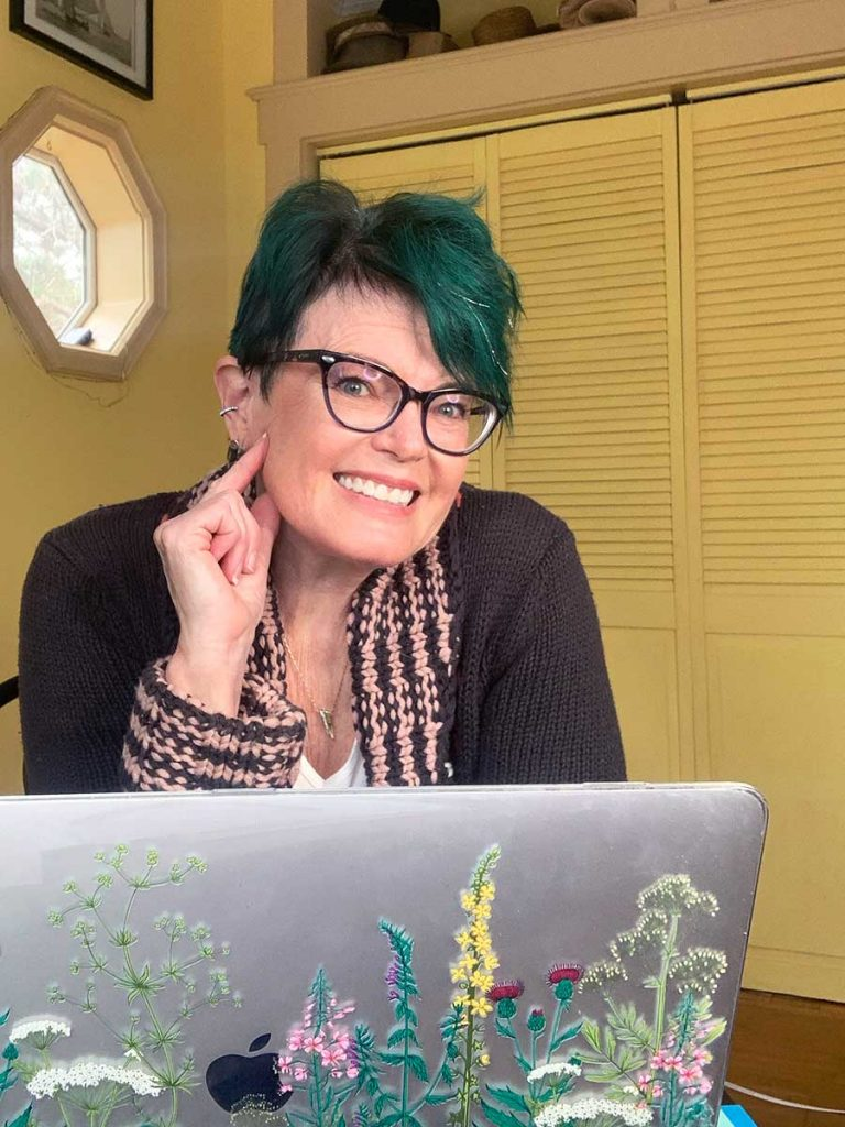 Robin Carberry smiling in her office at her laptop