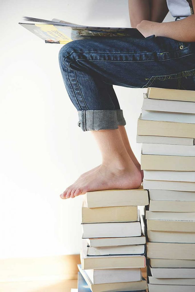 person sitting on a stack of books with her feet on a stack of books