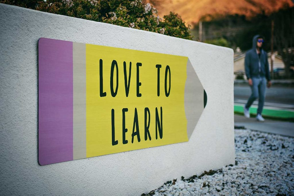 Love to Learn poster shaped like a pencil on a white exterior wall