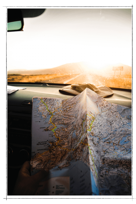 open map on the passenger side of a car driving towards mountains at sunset
